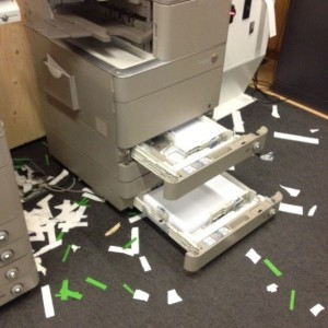 Scraps of paper scattered around a photocopier with the paper drawers open